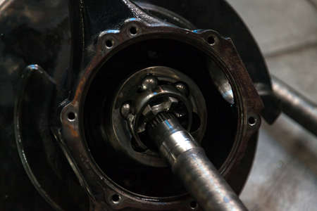 Close-up on a wheel joint from a car with a differential during repair, a used spare part. Auto service industry. Imagens