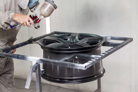 Painting the element body of the car - the aluminum alloy wheel with the help of aerograf in black color by the hand of painter repairman in the industrial professional garage. Auto service industry. Stock Photo