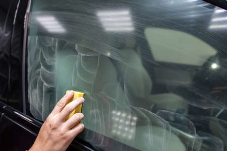 The man's hand applies a degreasing cleaner with a yellow sponge to the side window of the car to apply a protective nano ceramic coating. Auto service industry.