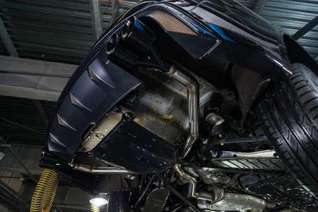Vue de dessous de la voiture sur un système d'échappement bifurqué, pare-chocs arrière avec diffuseur sport et buses en noir. Industrie du tuning et des services atomiques.