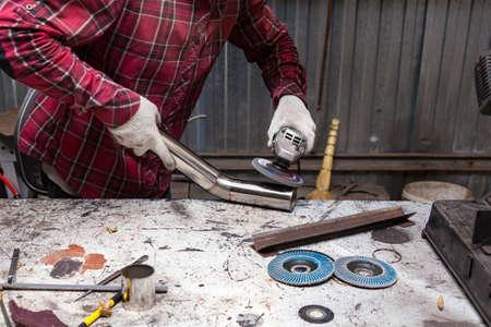 Oberflächenvorbereitung von Edelstahlrohren mit einem Winkelschleifer zum Weiterschweißen in einer Eisenwerkstatt. Industrie und Produktion.