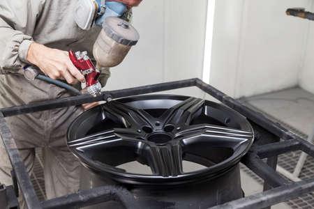 Dipingere l'elemento del corpo dell'auto - la ruota in lega di alluminio con l'aiuto dell'aerografo in colore nero dalla mano del riparatore del pittore nel garage professionale industriale. Industria dei servizi automobilistici.