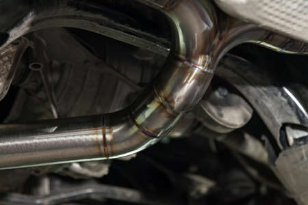 Fabrication and installation of a stainless steel car exhaust pipe with a bifurcation and a louder sound with a color weld under bottom. Tuning and auto service industry. 版權商用圖片 - 129697407