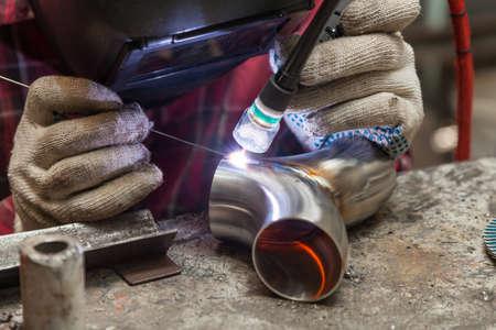 Un jeune soudeur vêtu d'une chemise rouge à carreaux soude un tuyau en acier inoxydable à l'aide d'une soudure agronomique pour protéger ses yeux avec un masque dans un atelier de fer. Méthodes de soudage modernes.