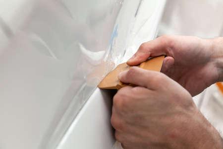 Reequipando el automóvil con una película protectora transparente sólida, el maestro alisa la superficie exprimiendo las burbujas de aire con un raspador, protegiendo los vehículos de arañazos y astillas en el taller.