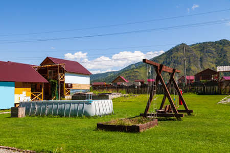 A large swing made of wood and an inflatable rubber pool on a green grass lawn in the courtyard of a country house with a wooden fence against the backdrop of the mountain and blue sky.