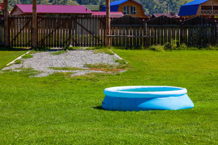 Blue inflatable rubber pool on a lawn of green grass in the courtyard of a country house with a wooden fence on a background of mountains and blue sky. 스톡 콘텐츠