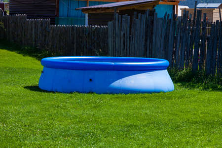 Piscina de goma inflable azul sobre un césped de hierba verde en el patio de una casa de campo con una valla de madera sobre un fondo de montañas y cielo azul. Foto de archivo
