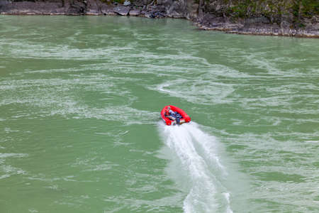 Aerial view of a red rubber motor boat sailing on a green river in the mountains between rocks and cliff Stock Photo