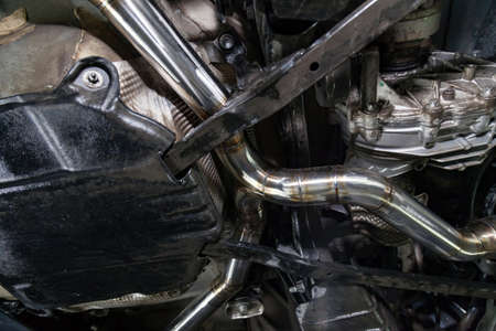 Fabrication and installation of a stainless steel car exhaust pipe with a bifurcation and a louder sound with a color weld under bottom. Tuning and auto service industry. 版權商用圖片 - 129698194