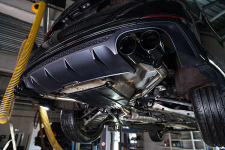 Bottom view of the car on a bifurcated exhaust system, rear bumper with a sports diffuser and nozzles in black. Tuning and atom service industry. Stock Photo