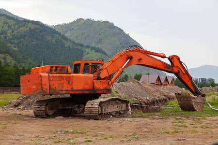 Large orange excavator with a lowered bucket during repair work in the mountains on a summer day. Stockfoto