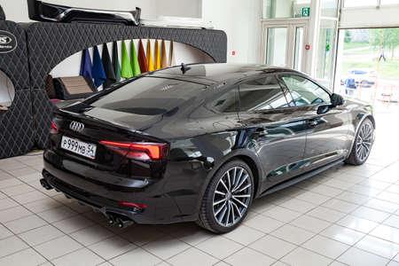 노보시비르스크, 러시아 - 08.01.2018: 2019 Audi A5 Sportback의 후면 보기가 판매를 위해 준비되어 광택이 나는 검은색 바디로 쇼룸에 전시되었습니다.