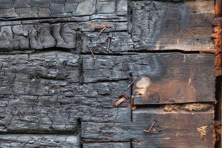 Background of a wall made of horizontal half-burned black boards in the form of coals with nails and self-tapping screws. Fire and extinguishing.