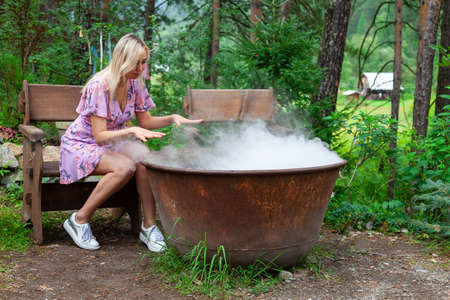 A young beautiful girl, a blonde witch is preparing a potion in a large cauldron on the eve of Halloween or the worshiping devil bringing in priesthood. Feminine witchcraft and influence on men.