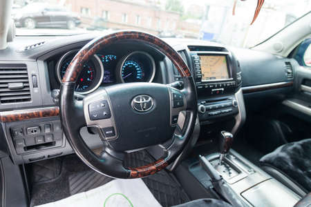 Novosibirsk, Russia - 08.09.2019: View to the interior of Toyota Land Cruiser 200 with dashboard, clock, media system, front seats, gray leather and shiftgear after cleaning before sale on parking Редакционное