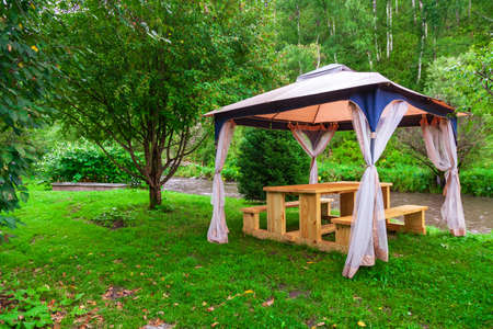 Outdoor tent with furniture in the forest with trees and green grass during an event, wedding or a celebration on a warm summer day. Stock Photo