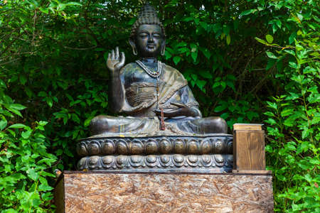 Buddha statue sitting in lotus position for worship and meditation of Buddhists in a flowering green garden with green trees and leaves. Religion and culture of the eastern countries.