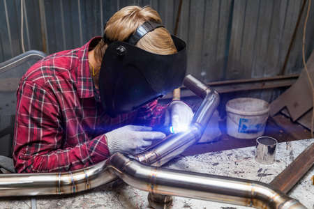 Young guy welder in a checkered red shirt welds a stainless steel pipe for car exhaust using agronomic welding to protect his eyes with a mask in an iron workshop. Modern welding methods. Banque d'images