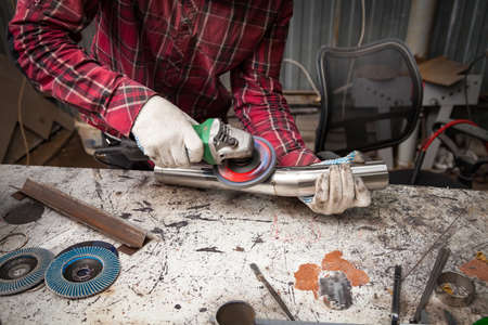 Surface preparation of stainless steel pipes using an angle grinder for further welding in an iron workshop. Industry and production. Banco de Imagens