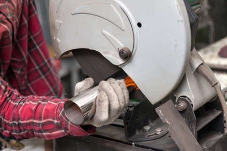 A male worker cuts a stainless steel pipe on a special machine for vertical sawing of metal parts for industrial use. Making exhaust for a car. 免版税图像