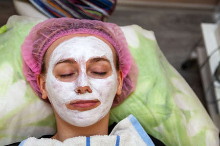 a mask of white cream on the face of a young girl who lies on the couch during facial cleansing and beauty treatments. Cabinet cosmetologist, skin health and youth