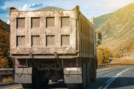 Rear view on a large dump truck rides on a highway in the mountains while transporting goods over long distances. Fast delivery by ground transportation. Stok Fotoğraf