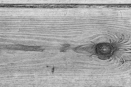 Tło o fakturze włókien drzewnych z czarno-białym sękiem w trybie monochromatycznym.