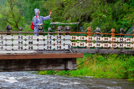 A young blonde girl in a blue raincoat is looking for a path on the navigator on the phone and on the map while traveling through wild places on a wooden suspension bridge over mountain river.