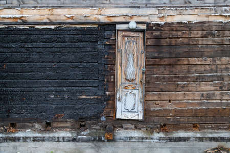 The wall of a wooden house made of timber is half burned up after a fire and covered with black coal in the middle of which is a narrow door. Cataclysms and disaster.