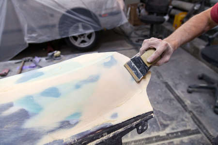 A man prepares a car body element for painting after an accident with the help of grinding abrasive paper in a car repair shop. Recovery bumper after a collision.