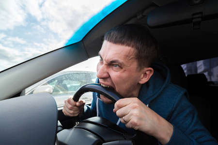 An unbalanced, goosey man bites a car steering wheel from anger while driving in a traffic jam or after an accident. A nervous and nutty guy cannot restrain his emotions and yells at other road users. Imagens
