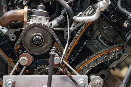 Nahaufnahme eines zerlegten Motors mit Blick auf Gasverteilungsmechanismus, Kette, Zahnräder und Spanner während der Reparatur und Restaurierung nach einer Panne. Auto-Service-Branche. Standard-Bild
