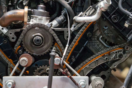Zbliżenie na zdemontowany silnik z widokiem na mechanizm dystrybucji gazu, łańcuch, koła zębate i napinacze podczas naprawy i renowacji po awarii. Branża usług samochodowych. Zdjęcie Seryjne