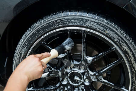 A male worker washes a black car with a special brush for cast wheels and scrubs the surface to shine in a vehicle detailing workshop. Auto service industry.