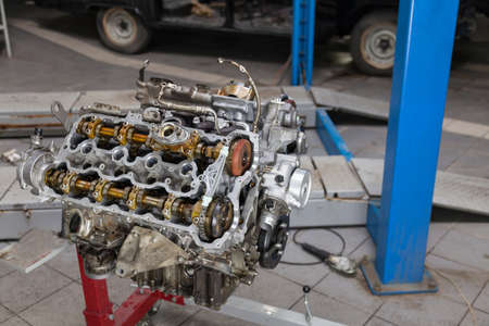 Replacement used engine mounted on a crane for installation on a car after a breakdown and repair in a car repair workshop as a guarantee for the dealership. Auto service industry.