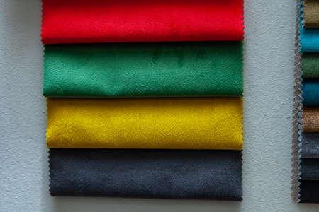 Pieces of textile material for interior trim and furniture making for example in the catalog of different colors for the design studio. Many colored materials hanging on the wall in stock.