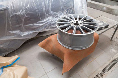Preparing the surface of the aluminum disk of the car for subsequent painting in the workshop, cleaning and leveling the wheel with the help of abrasive material. Auto service industry.