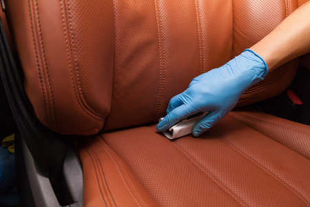 Applying a nano-ceramic coating for interior Leather on the cars seat brown upholstery by a worker with a sponge and chemical composition in blue gloves 写真素材
