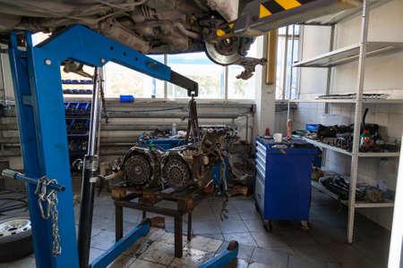 Blue lift crane with car engine in auto service workshop