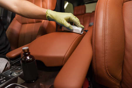 Applying a nano-ceramic coating for interior leather on the cars seat brown upholstery by a worker in yellow gloves with a sponge and bottle of chemical composition. Auto service industry. 写真素材