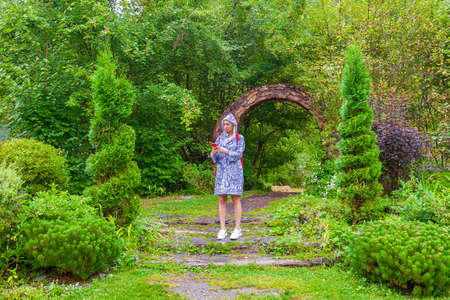 A young blonde girl in a blue raincoat with a phone in park or forest on summer day with green bushes. Travelling and navigation. Standard-Bild - 130758067