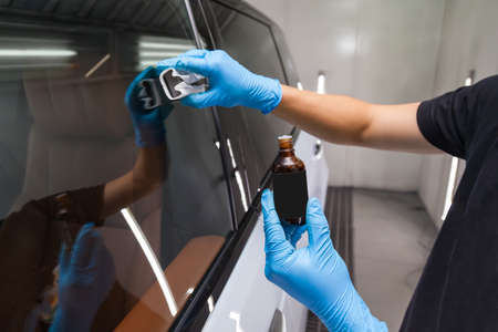 The process of applying a nano-ceramic coating for hydrophobic effect on the car's windows by a male worker with a sponge and 
