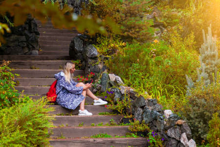 Young beautiful blonde girl in a blue raincoat sits on a wooden staircase with stone walls in a yellow autumn flowered garden texting on social networks via phone and taking a selfie on fall time.