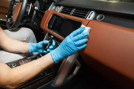 Applying a nano-ceramic coating for interior leather on the cars seat brown upholstery by a worker in blue gloves with a sponge and bottle of chemical composition. Auto service industry.