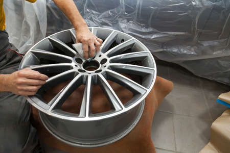 Master body repair man is working on preparing the surface of the aluminum wheel of the car for subsequent painting in the workshop, cleaning and leveling the disk with the help of abrasive material