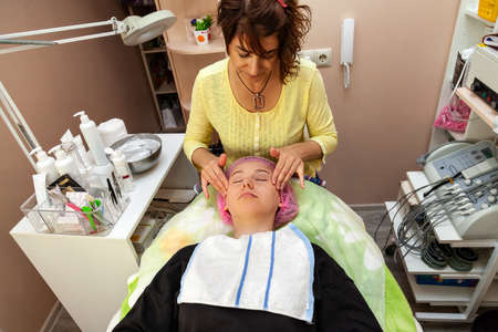A young girl is lying on a couch during cosmetic procedures with a beautician woman making massage. Cleansing, cosmetology and make up.
