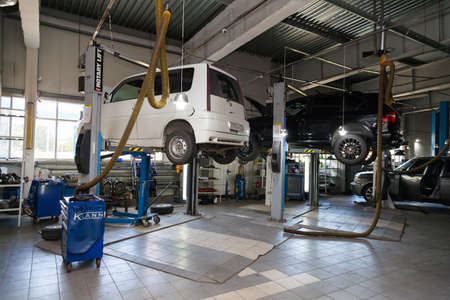 Novosibirsk, Russia - 08.01.2018: Two used cars with an open hood raised on a lift for repairing the chassis and engine in a vehicle repair shop. Auto service industry.