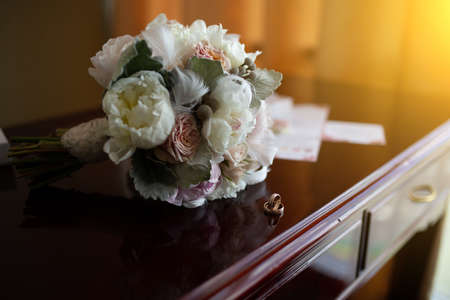 Wedding bouquet of peonies and roses lying on a wooden vintage table near wedding rings on the background of the invitation in the apartments to prepare the bride and expectation of the groom. Stockfoto