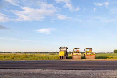 Three large yellow asphalt compactor standing on the side of the track during highway road repair and laying black new asphalt against a landscape with a blue sky and clouds in the summer. Stock Photo